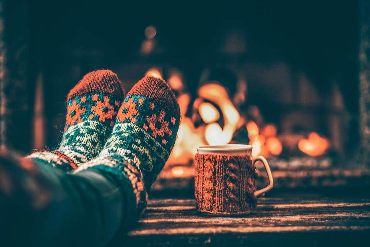 Feet in woollen socks by the Christmas fireplace.
